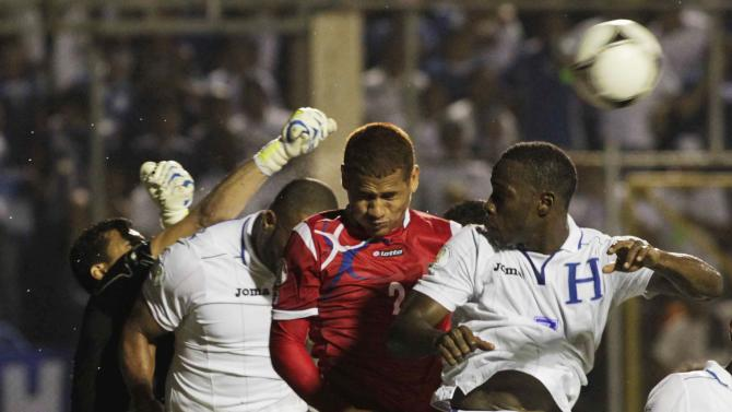 Honduras' Valladares clears the ball as Bernardez and Figueroa pressure Panama's Chen during their 2014 World Cup qualifying soccer match in Tegucigalpa