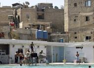 File picture shows Palestinian youths enjoy the water at al-Bassel swimming pool in the heart of the Palestinian refugee camp of Yarmuk o the outskirts of Damascus. The half a million Palestinian refugees living in Syria should keep out of the country's conflict and their neutrality be respected, UN Relief and Works Agency chief Filippo Grandi told AFP