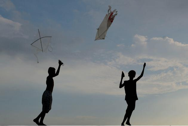 Boys are silhouetted as they fly their kites during summer school break in Navotas