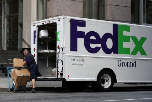 A FedEx worker loads a cart with packages to be delivered in September 2012 in San Francisco, California. FedEx and United Parcel Service are being investigated by the Securities and Exchange Commission (SEC) in a probe of prescription medication sales by online pharmacies, the two US package delivery companies said.