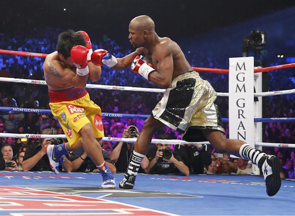 Pacquiao of the Philippines covers his face as he is punched by Mayweather, Jr. of the U.S. in the first round during their welterweight WBO, WBC and WBA (Super) title fight in Las Vegas