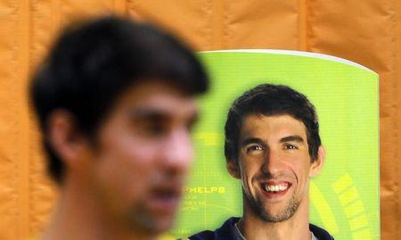 U.S. swimmer Michael Phelps stands next to a banner with his image during a promotional event in Sao Paulo