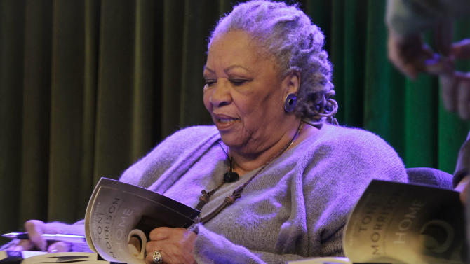 """Author Toni Morrison signs copies of her latest book """"Home,"""" during Google's online program series, Authors At Google, on Wednesday, Feb. 27, 2013 in New York.  (AP Photo/Bebeto Matthews)"""