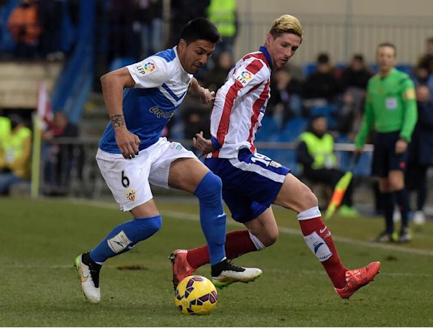Almeria defender Mauro Javier dos Santos (L) is challenged by Atletico Madrid forward Fernando Torres during a Spanish La Liga match at the Vicente Calderon stadium in Madrid, on February 21, 2015