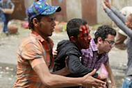 Egyptian anti-military protesters help a wounded demonstrator during clashes in the Abbassiya district of Cairo