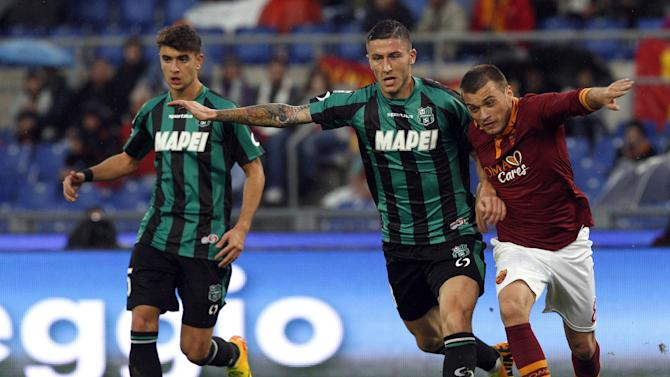 Sassuolo midfielder Luca Marrone, center, and AS Roma forward Adem Ljajic, of Serbia, right, fight for the ball during a Serie A soccer match between AS Roma and Sassuolo at Rome's Olympic stadium, Sunday, Nov. 10, 2013