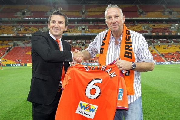 BRISBANE, AUSTRALIA - NOVEMBER 20:  Former English Cricket player Ian Botham is presented with a Brisbane Roar jersey by Roar player Shane Stefanutto before the round 15 A-League match between the Bri