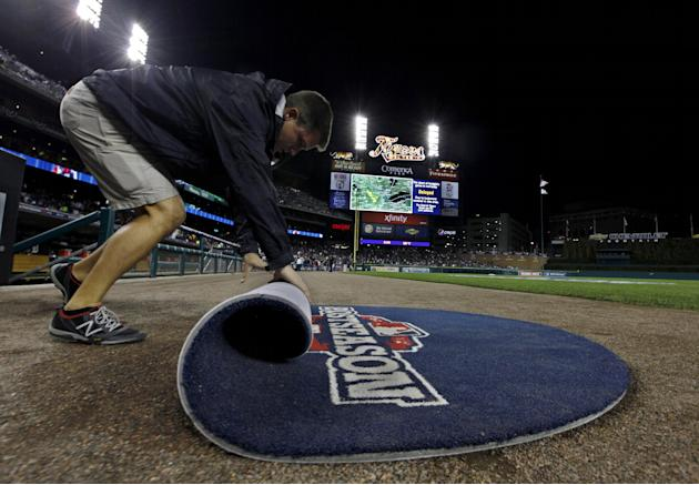 A grounds crew member rolls up the on-deck circle mat during a rain delay at Game 4 of the American League championship series between the Detroit Tigers and New York Yankees Wednesday, Oct. 17, 2012,