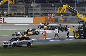 The car of Gutierrez of Mexico is removed from the track after his collision with Maldonado of Venezuela during the Bahrain F1 Grand Prix at the Bahrain International Circuit (BIC) in Sakhir