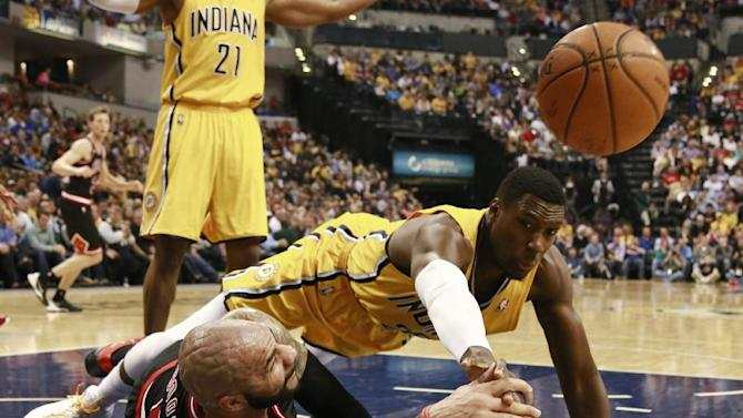 Chicago Bulls forward Carlos Booozer, left, passes the basketball as Indiana Pacers center Ian Mahinmi dives for it in the first half of an NBA basketball game in Indianapolis, Friday, March 21, 2014