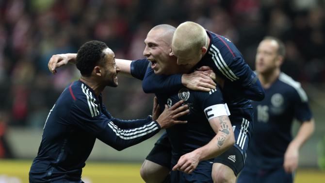 Brown of Scotland celebrates with his teammates Anya and Naismith after scoring a goal against Poland during their international friendly match in Warsaw