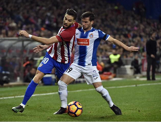 Atletico Madrid's forward Yannick Ferreira Carrasco (L) vies with Espanyol's midfielder Pablo Piatti during the Spanish league football match December 3, 2016