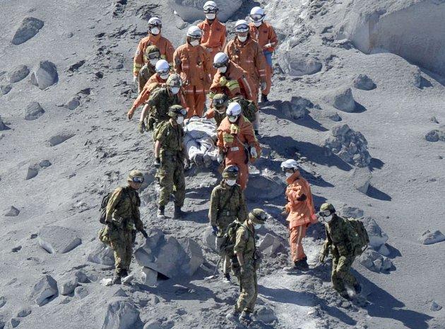 Japan Self-Defense Force (JSDF) soldiers and firefighters carry an injured person near a crater of Mt. Ontake, which straddles Nagano and Gifu prefectures in this September 28, 2014 photo taken and released by Kyodo. More than 500 Japanese military and police set out on Sunday to search the peak of a volcano popular with hikers a day after its sudden eruption trapped hundreds on the mountain for hours, amid conflicting reports about missing and injured climbers. Mandatory credit. REUTERS/Kyodo (JAPAN - Tags: DISASTER ENVIRONMENT SOCIETY) ATTENTION EDITORS - THIS IMAGE HAS BEEN SUPPLIED BY A THIRD PARTY. THIS PICTURE WAS PROCESSED BY REUTERS TO ENHANCE QUALITY. AN UNPROCESSED VERSION WILL BE PROVIDED SEPARATELY. MANDATORY CREDIT. JAPAN OUT. NO COMMERCIAL OR EDITORIAL SALES IN JAPAN. YES