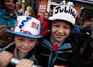 Children wearing homemade crowns await the arrival of Britain's Queen Elizabeth II at St Macartin's Church of Ireland Cathedral in Enniskillen, Northern Ireland. The queen shook hands with former IRA commander Martin McGuinness in a highly symbolic moment in the Northern Ireland peace process