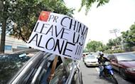 A motorist displays an anti-China placard in front of the Chinese consulate in Manila. Hundreds of Filipinos demonstrated outside the Chinese embassy in the Philippines over an escalating territorial row, with the protesters denouncing China's rulers as arrogant bullies