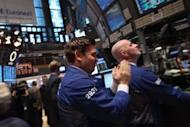 A trader applauds while working on the floor of the New York Stock Exchange on February 21. The blue-chip Dow Jones Industrial Average closed Tuesday above 13,000 for the first time in nearly five years, as Wall Street stocks rallied on a mixed bag of economic news