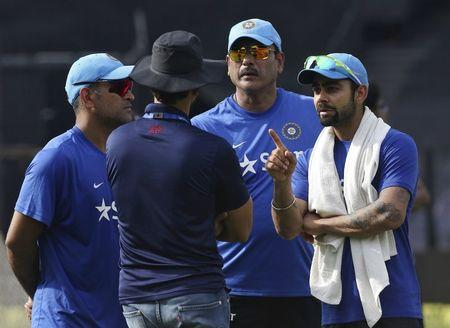 India's Kohli talks with team selector Rathour as captain Dhoni and team director Shastri look on during a practice session ahead of their Twenty20 cricket match against South Africa in Kolkata
