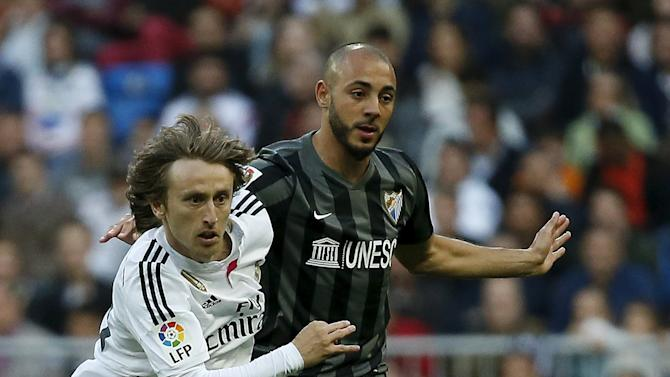 Real Madrid's Luka Modric battles for the ball with Malaga's Nordin Amrabat during their Spanish First Division soccer match at Santiago Bernabeu stadium in Madrid