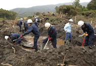 Fire brigade members search for missing people on October 21, 2013 after a landslide caused by heavy rains from Typhoon Wipha hit Oshima island