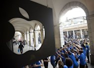 Apple Store employees create a tunnel for customers as they are allowed into the shop to buy the new iPhone 5 at Covent Garden in London