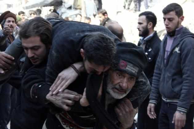 A man carries an injured man that survived from under the debris of collapsed buildings after what activists said were air strikes by forces loyal to Syria's President Bashar al-Assad in Arbeen, i