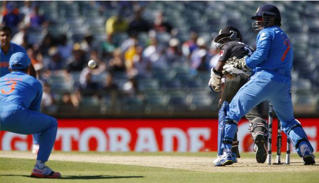 India's Suresh Raina prepares to catch out UAE's batsman Krishna Karate as India's wicket keeper MS Dhoni watches during their Cricket World Cup match in Perth