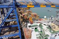 "A container ship is unloaded at the Mundra Port and Special Economic Zone (MPSEZL) at Mundra in 2011. India on Friday said its trade deficit was ""ballooning"" after imports sharply outpaced exports last month"