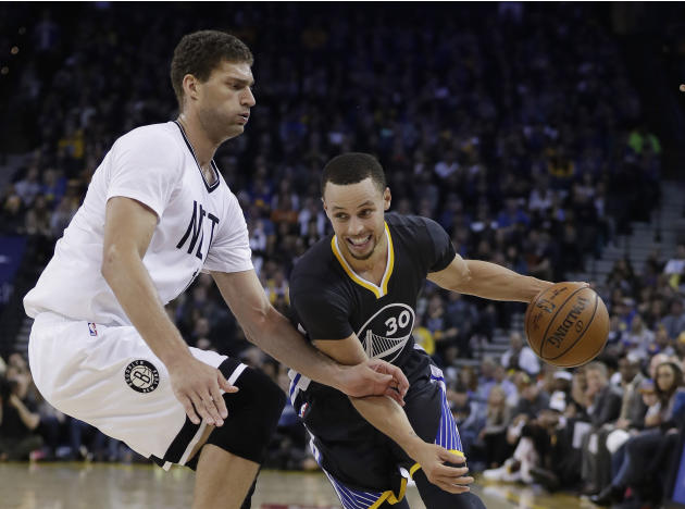Golden State Warriors' Stephen Curry (30) dribbles past Brooklyn Nets' Brook Lopez during the first half of an NBA basketball game Saturday, Feb. 25, 2017, in Oakland, Calif. (AP Photo/Marcio