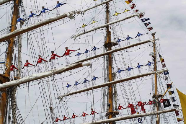 "Crew members of Colombian-registered sailing ship Gloria stand on the ship's masts during a welcome ceremony of the ""Velas de America"" sailing encounter in Callao port"