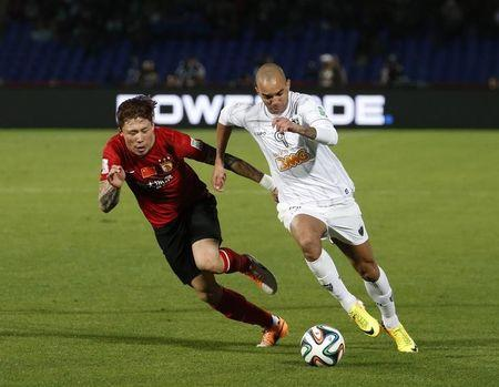Diego Tardelli of Brazil's Atletico Mineiro fights for the ball with Zhang Linpeng of China's Guangzhou Evergrande during their 2013 FIFA Club World Cup third place soccer match at Marrakech stadium