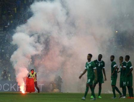 Police officer extinguishes a flare on the pitch during the 2018 World Cup qualifying soccer match between Malaysia and Saudi Arabia in Kuala Lumpur, Malaysia