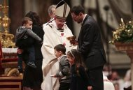 Pope Francis looks at a family during the Christmas night mass in the Saint Peter's Basilica at the Vatican December 24, 2013. REUTERS/Tony Gentile