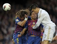 "Barcelona's Carles Puyol (L) and Thiago Alcantara (C) jump for the ball against Real Madrid's Cristiano Ronaldo during the Spanish League ""El clasico"" football match at the Camp Nou stadium in Barcelona. Real Madrid won 2-1"