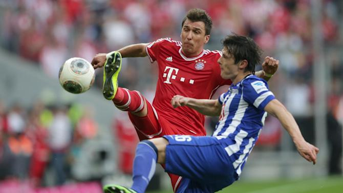 Bayern's Mario Mandzukic of Croatia, left, and Berlin's Nico Schulz challenge for the ball during the German first division Bundesliga soccer match between FC Bayern Munich and Hertha BSC Berlin, in Munich, southern Germany, Saturday, Oct. 26, 2013