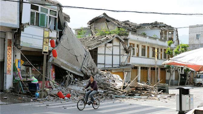 In this photo released by China's Xinhua News Agency, a local resident bicycles in front of collapsed houses after an earthquake struck in Lushan County, Ya'an City, in southwest China's Sichuan Province, Saturday, April 20, 2013. A powerful earthquake struck the steep hills of China's southwestern Sichuan province Saturday morning, leaving at least 160 people dead and more than 6,700 injured. (AP Photo/Xinhua, Jin Xiaoming) NO SALES