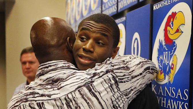 Kansas freshman NCAA college basketball player Andrew Wiggins, right, hugs his father Mitchell Wiggins, left, following a news conference at the University of Kansas in Lawrence, Kan., Monday, March 31, 2014. Wiggins announced he would be entering the NBA draft