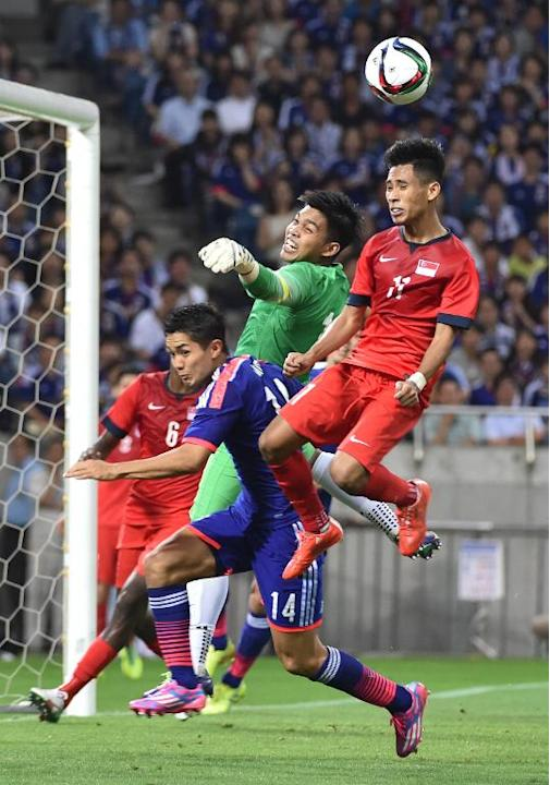 Singapore's goalkeeper Mohamad Izwan Bin Mahbud (C) and Muhammad Nazrul Bin Ahmad Nazari (R) fight for the ball against Japan's forward Yoshinori Muto during the 2018 FIFA World Cup football q