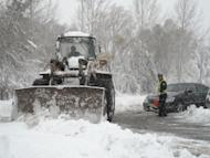 A worker uses a bulldozer to clear a snow-covered street after heavy snow-fall in the outskirts of Beijing on November 4. The bodies of five street children have been found in a dumpster in southwest China after they climbed inside it to escape the night-time cold, state media reported Sunday