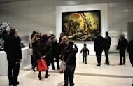 """People stand in front of Eugene Delacroix's masterpiece """"Liberty Leading the People"""" on display in Lens, northern France, on December 4, 2012. Specialists have been able to """"completely remove"""" marks left by a defacement of one of the most iconic paintings in French history, according to the Louvre"""