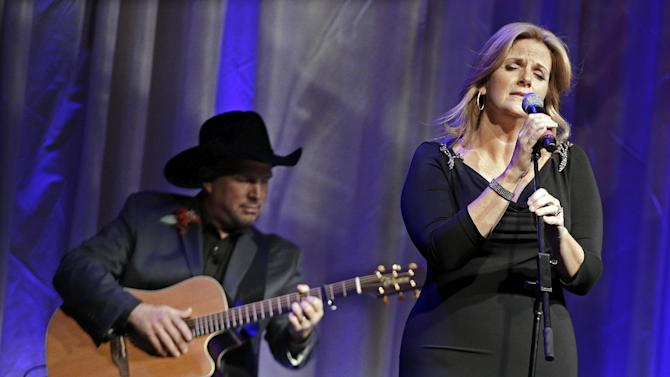 """Trisha Yearwood is accompanied by her husband, Garth Brooks, as she sings """"Wind Beneath My Wings,"""" a song written by Larry Henley, as Henley is inducted into the Nashville Songwriters Hall of Fame on Sunday, Oct. 7, 2012, in Nashville, Tenn. (AP Photo/Mark Humphrey)"""