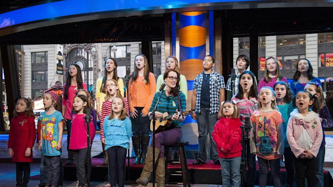 "Ingrid Michaelson accompanied by children from Newtown, Conn. and Sandy Hook Elementary school perform ""Somewhere Over the Rainbow"" on ABC's ""Good Morning America"" on Tuesday, Jan. 15, 2013 in New York.  The Children who survived last month's shooting rampage, recorded a version of ""Over the Rainbow"" to raise money for charity.  They recorded the song at the home of two former members of the Talking Heads rock band. It went on sale Tuesday on Amazon and iTunes, with proceeds benefiting a local United Way and the Newtown Youth Academy. (Photo by Charles Sykes/Invision/AP)"