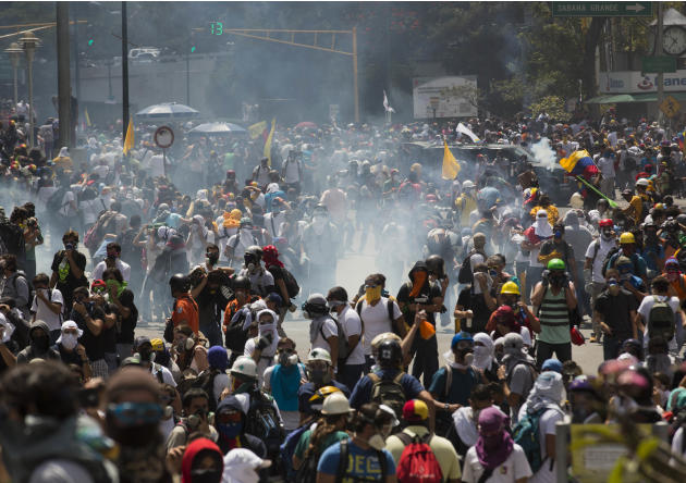 Anti-government demonstrators run from a cloud of tear gas fired at them by Bolivarian National Police during clashes at the Central University of Venezuela, UCV, in Caracas, Venezuela, Thursday, Marc