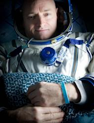 """Expedition 26 Commander Scott Kelly wears a blue wrist band that has a peace symbol, a heart and the word """"Gabby"""" to show his love of his sister-in-law U.S. Rep. Gabrielle Giffords as he rests shortly after he and cosmonauts Oleg Skripochka and"""