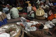 Indian passengers and vendors wait on the platform of Sealdah train station for the resumption of services during a power failure in Kolkata
