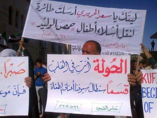 "Residents of Syria's Hass holding up signs that reads in Arabic, ""Houla you are in our hearts"""