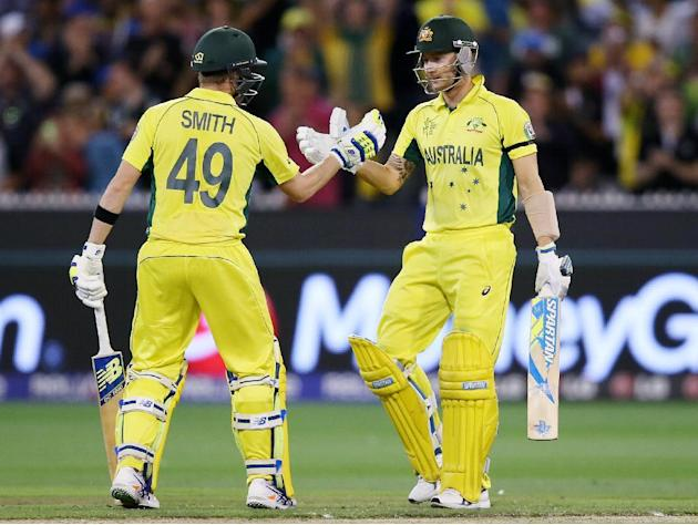 Australian captain Michael Clarke, right, is congratulated by teammate Steve Smith after scoring 50 runs while batting against New Zealand during the Cricket World Cup final in Melbourne, Australia, S