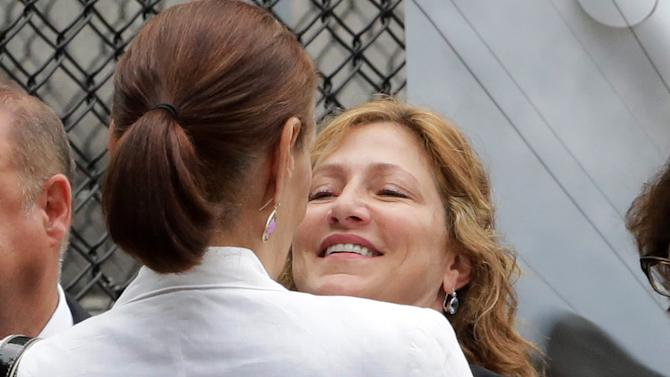 """Actress Edie Falco embraces a woman as she arrives for the funeral service of James Gandolfini, star of """"The Sopranos,"""" in New York's the Cathedral Church of Saint John the Divine, Thursday, June 27, 2013. The 51-year-old actor died of a heart attack last week while vacationing in Italy with his son.(AP Photo/Richard Drew)"""