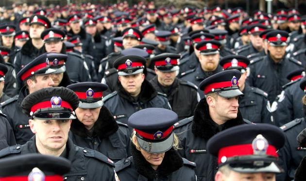 Officers file into a public memorial for police constable John Zivcic in Toronto