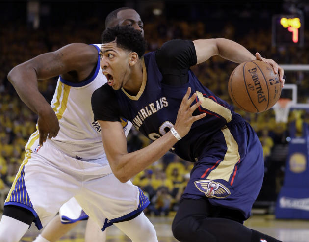 New Orleans Pelicans' Anthony Davis, right, drives past Golden State Warriors' Draymond Green during the second half in Game 1 of the NBA basketball playoffs Saturday, April 18, 2015, in Oakla