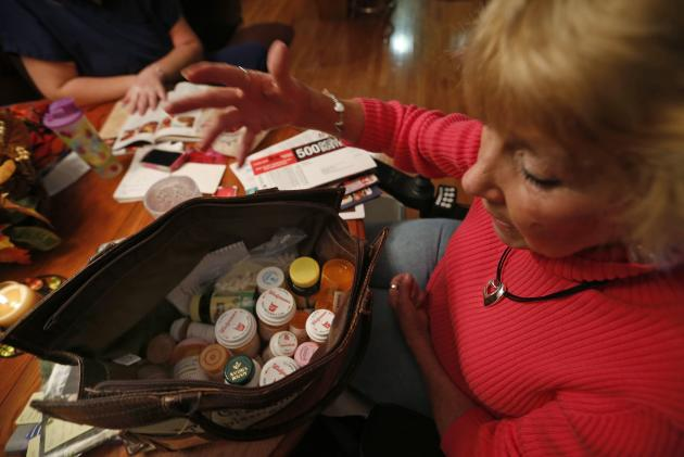 REFILE - ADDING REFERENCE TO ACCOUNTABLE CARE ORGANIZATIONS Sandy Wright looks over her bag of medications at her home in Peoria, Illinois, November 25, 2013. Wright has Neuromyelitis Optica and has a Certified Nursing Assistant come to help her around the house. Now, patients like Wright are at the forefront of an experiment, under way in Peoria, Illinois, and hundreds of other U.S. cities, that could transform the way doctors, nurses and hospitals deliver care to patients. Amid the barrage of criticism over the rollout of Obamacare, groups known as Accountable Care Organizations (ACOs) are quietly going about the business of testing the potential for healthcare reform. The efforts, born of President Barack Obama's Affordable Care Act, are part of the biggest experiment yet to fix the costly and error-plagued U.S. healthcare system. The new models of care, which encourage providers to form networks to coordinate care and cut costs, involve close monitoring of the sickest patients to address budding health problems before they cause a costly trip to the emergency room or an extended hospital stay. To match Feature USA-HEALTHCARE/PEORIA Picture taken November 25, 2013. REUTERS/Jim Young (UNITED STATES - Tags: HEALTH POLITICS)
